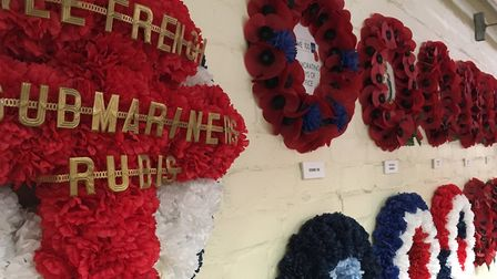 Regimental, commemorative and civilian wreaths on the factory wall. Image by Claire Saul