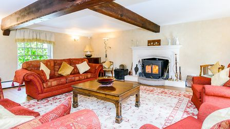 Huge beams and impressive fireplace, yet still cosy in the living room (photo: Savills)