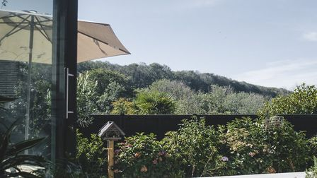 The sun-soaked terrace provides the perfect view over the garden and beyond. Photo: Steve Haywood