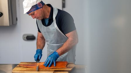 John shows care and attention as he prepares the fish. Photo: Jim Wileman