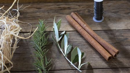 Materials for napkin rings - raffia, rosemary, olive, cinnamon sticks and reel of wire