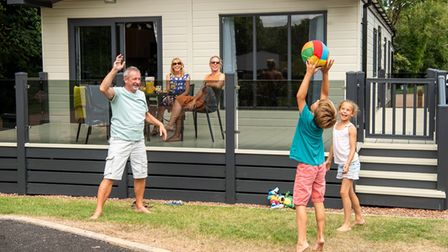Family playing ball games outside a chalet at HoburneDevon Bay
