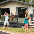 Family playing ball games outside a chalet at Hoburne Devon Bay