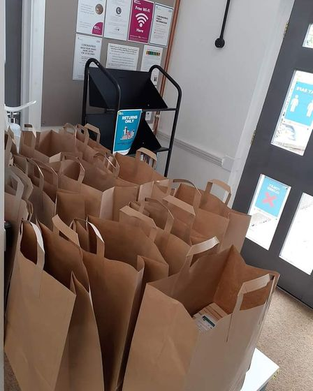 Bags of books waiting to be collected with a free postcard inside