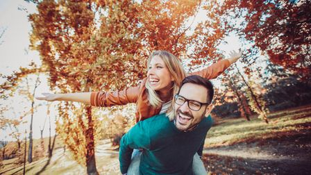 Couple in love in autumn.Smiling young couple hugging in the park.