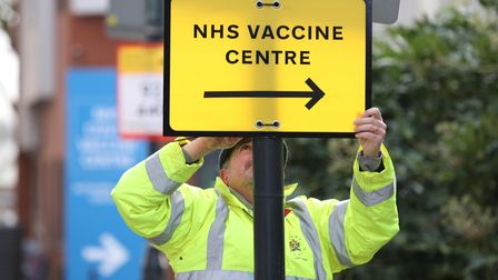 A Brent Council worker hangs a direction sign to the NHS Covid Vaccine Centre at the Olympic Office