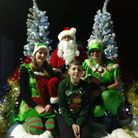 Santa and his elves on the back of a truck with Christmas trees and decorations