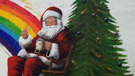 Painting of Father Christmas with a tree and a rainbow