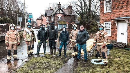Volunteers and fir fighters clearing flood water in Park Street, St Albans