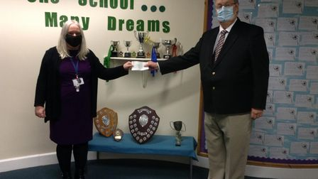Mrs Clare Fegan, head of Sidmouth Primary, accepts the cheque from the Rotary Club of Sidmouth