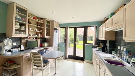 kitchen with white tiled floor and beige wall and floor units with shelving above the grey-green worktops on the left and...