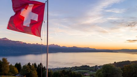 A Swiss flag is seen floating at sunset above Lake Geneva