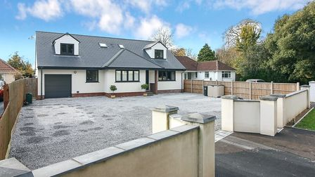 white bungalow with two dormers either end and integral garage on left and big grey driveway garden with wall and gateway...