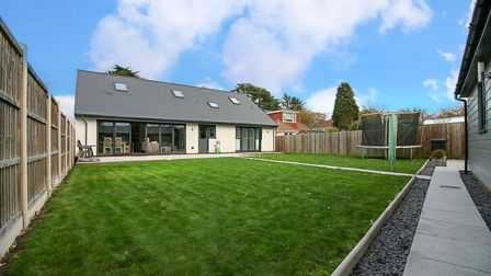 back of bungalow with bi-folding doors taking up left-hand side, roof windows and immaculate lawn in front with fence down...