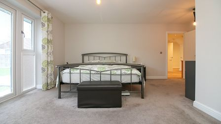 bedroom with double bed with metal bedframe and blanket box in front, beige carpet and cream walls and French doors on the left and door at the back on right