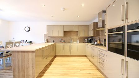 beige kitchen in a rectangular shape to separate it from the dining area with black eye-level double ovens on right in foreground