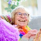 Smiling older woman looking at the camera in a care home setting with colourful costume during a group activity