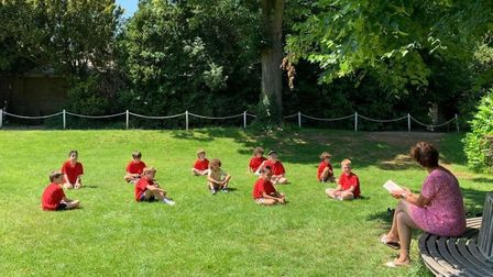 Group of children learning outside on the grass