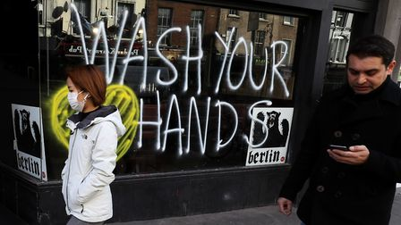 People pass graffiti reminding people to wash their hands on the window of a bar in Dublin's city ce