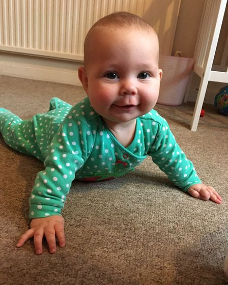 baby laying down in green babygrow