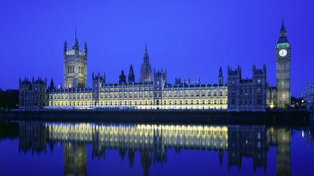 The Houses of Parliament - a view from the south bank of the river Thames at night with reflection i