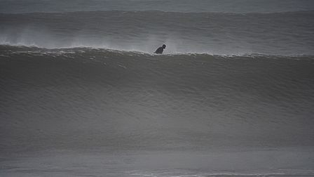 A surfer pops up between the big waves at Croyde