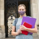Portrait Of Female Student Standing Outside College Or University Building Wearing Face Mask During