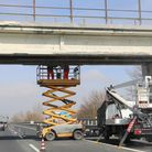 men at work to maintenance a bridge over highway