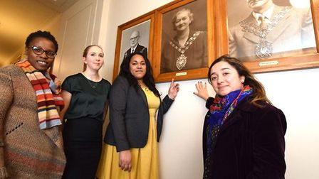 Hackney women councillors standing next to photograph of Hackney's first female mayor.