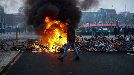 Rising anger: Protesters lay bikes down to block a street and set a fire during a protest against the coronavirus measures in Eindhoven in January