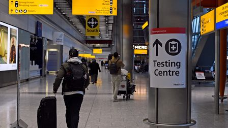 A passenger walks past a sign for the covid testing centre in the Arrival Hall of Terminal 5 at Lond