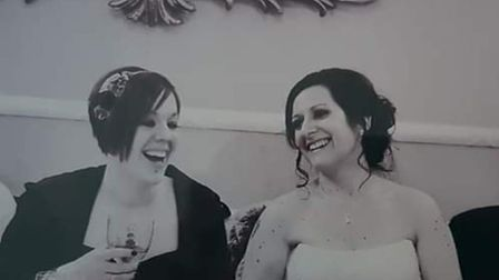 Black and white photo of Vicky Lovelace-Collins and Naomi Collins laughing on their wedding day