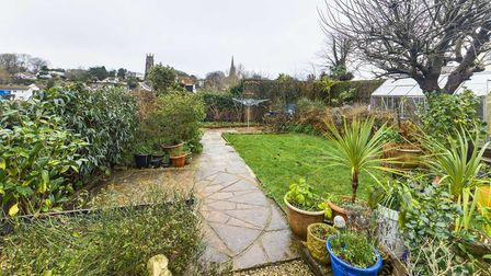 An enclosed level rear garden has a paved patio area and lawn with wide, well-stocked border beds