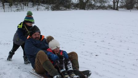 Dad and two sons sledging