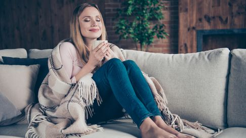 Woman sat on sofa wrapped up warm with a cup of tea