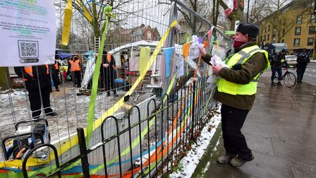 A council officer removes letters of support and other notices from the front fence of Dixon Clark Court at Highbury Corner