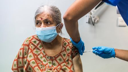 An older woman gets vaccinated.