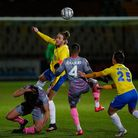 Asa Hall, Captain of Torquay United wins the aerial challenge against Jerome Okimo, Captain of Weal