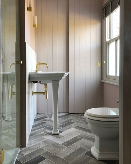 Scuffed brass taps, an elegant console basin and a tiled herringbone floor give timeless style to this en suite bathroom...