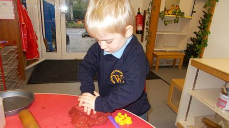 Child playing with red paint at nursery