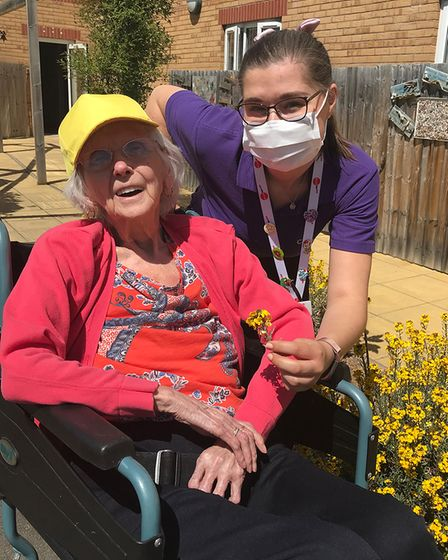 Picture of a member of the care staff with a Trymview Hall resident outside in the sunshine