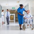 Senior female woman patient in wheelchair sitting in hospital corridor with African American female