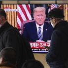 Masked people walk in front of a TV screen showing a live broadcast of U.S. President Donald Trump's
