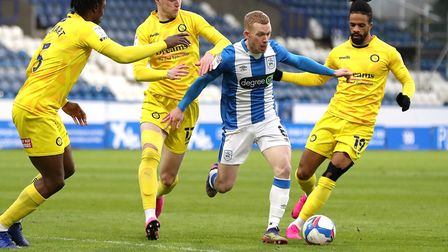 Huddersfield Town's Lewis O'Brien (centre) battles for the ball with Wycombe Wanderers' Anthony Stew