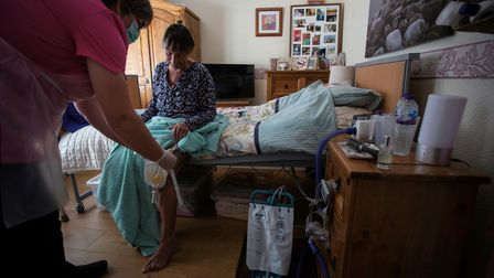 Dawn, a carer,tends to her client Tina during a home visit in Scunthorpe