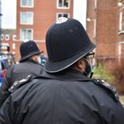 Two police men walk around a residential area.