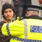Police arrest and handcuff protester Alex Sidney as he comes down from the crane on Duke Street in Norwich.