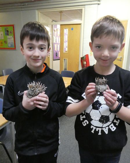 Two students with clay hedgehogs