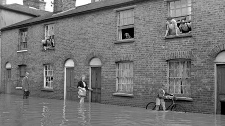 People and a dog, who are marooned in upper rooms, look down on a watery scene in flooded Friars Roa