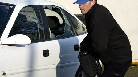 A thief breaks into a car during a mock-up by the Police Service of Northern Ireland in Belfast, Mon